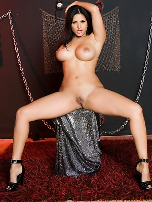 Sunny Leone unzips her sexy plaid bra corset and poses naked amongst the chains and manacles of her private sex dungeon!